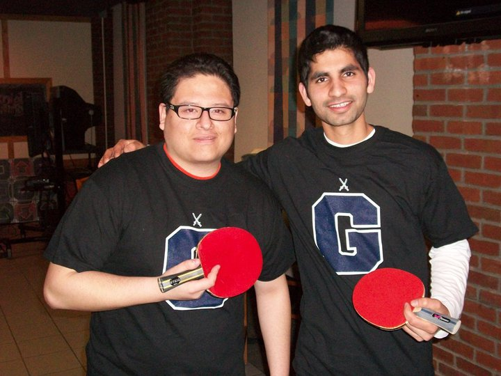 Two students holding ping pong paddles