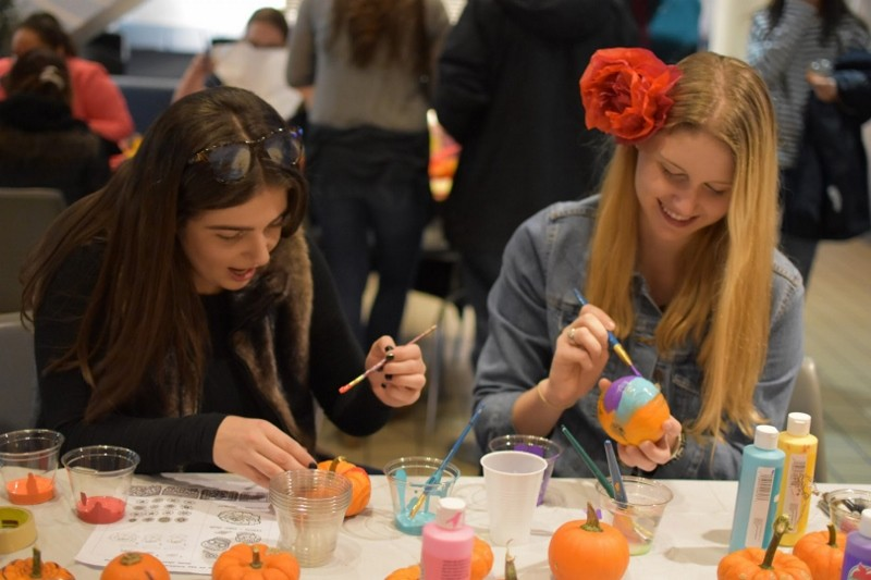 Salsa Con Salsa event, two students painting mini pumpkins