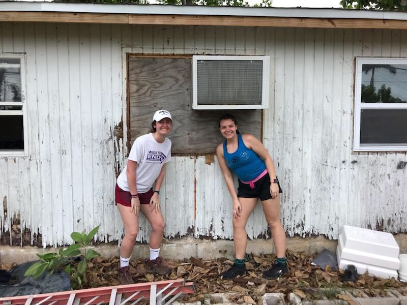 Two Volunteers in front of their worksite.