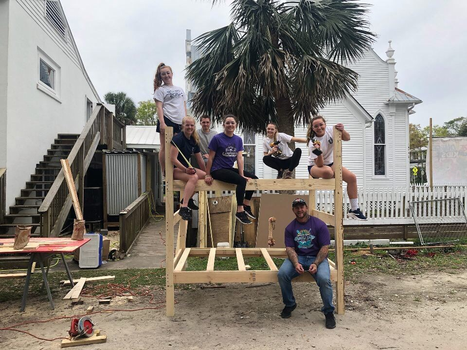 Group picture of volunteers and host organizer on a bunk bed in progress of being built