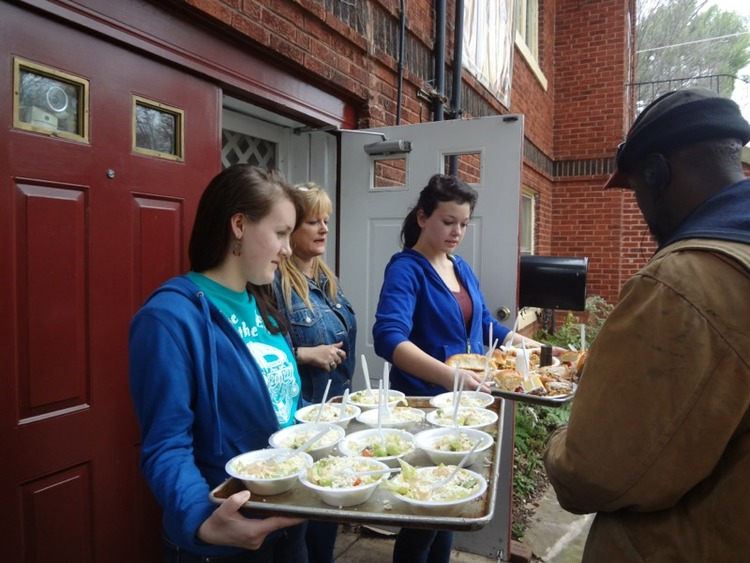 Students serving food at a soup kitchen