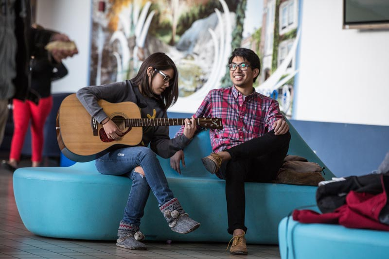 Two students enjoying guitar in the Union.