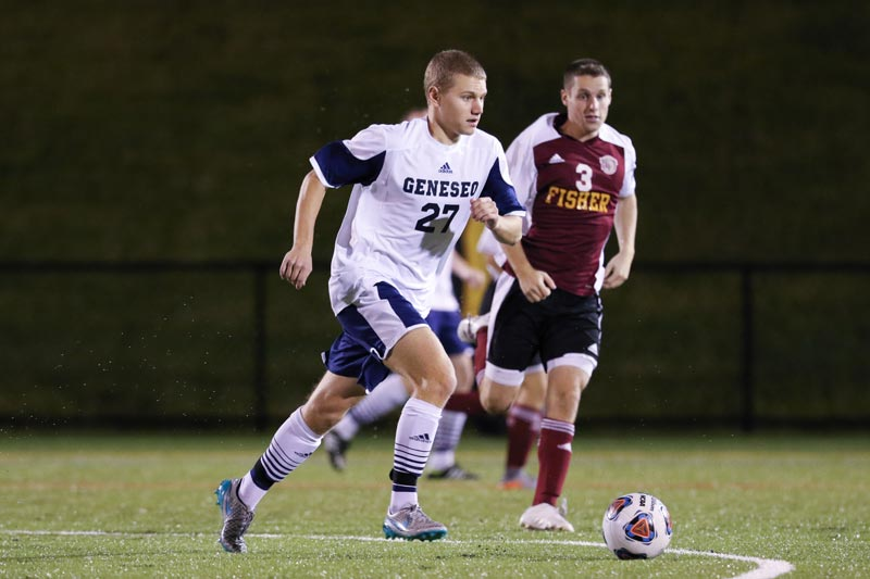 A SUNY Geneseo men's soccer player runs with the ball during a game.