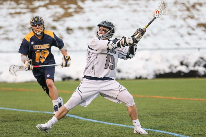 A SUNY Geneseo men's lacrosse player on the field during a game.