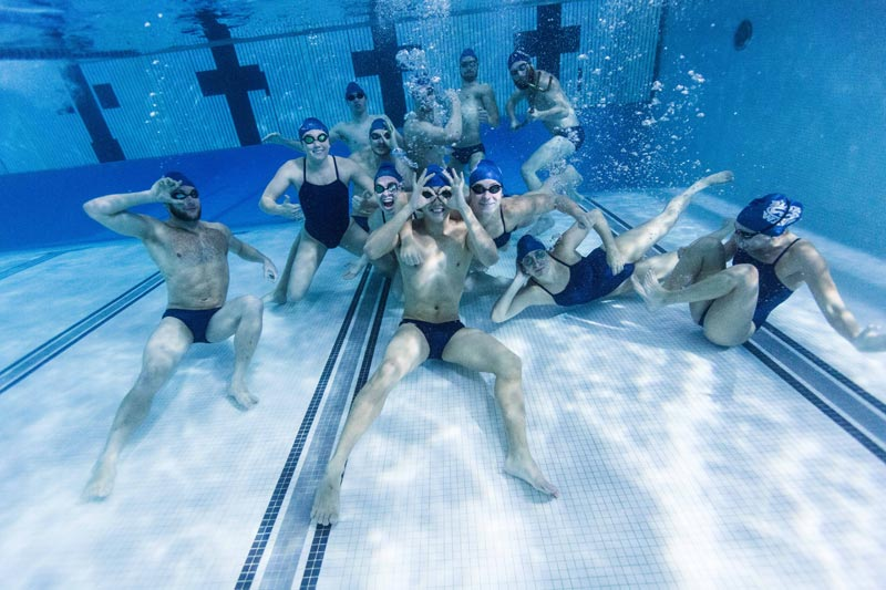 The Blue Wave swim team at SUNY Geneseo, posing underwater.