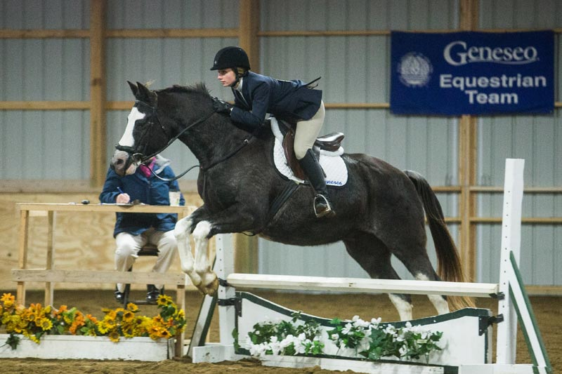 A member of the SUNY Geneseo equestrian team executes a jump on her horse.