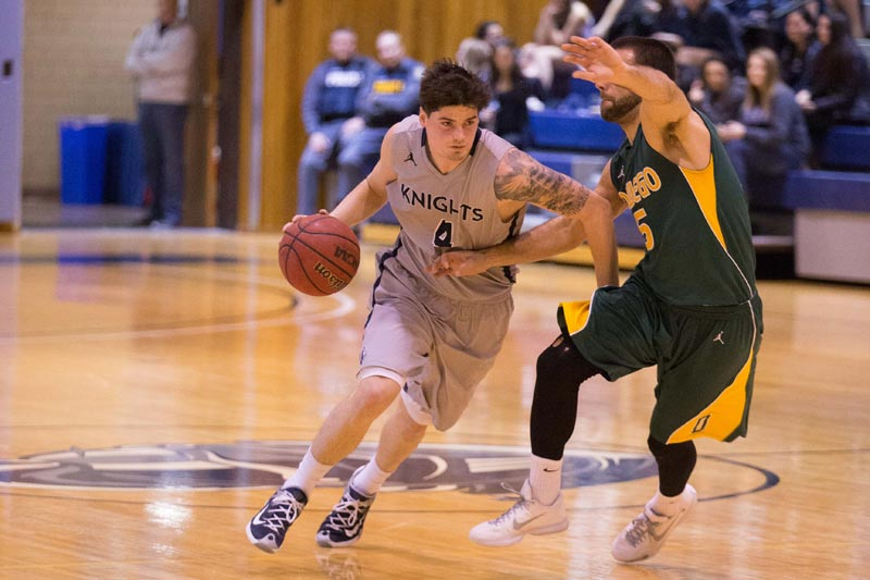 A SUNY Geneseo men's basketball player approaches the basket during a game.