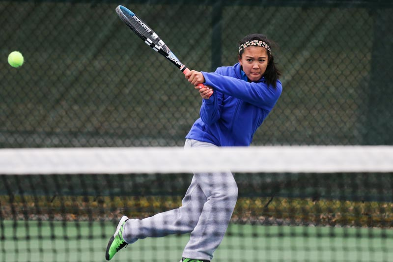 A SUNY Geneseo tennis player lobs the ball across the net.
