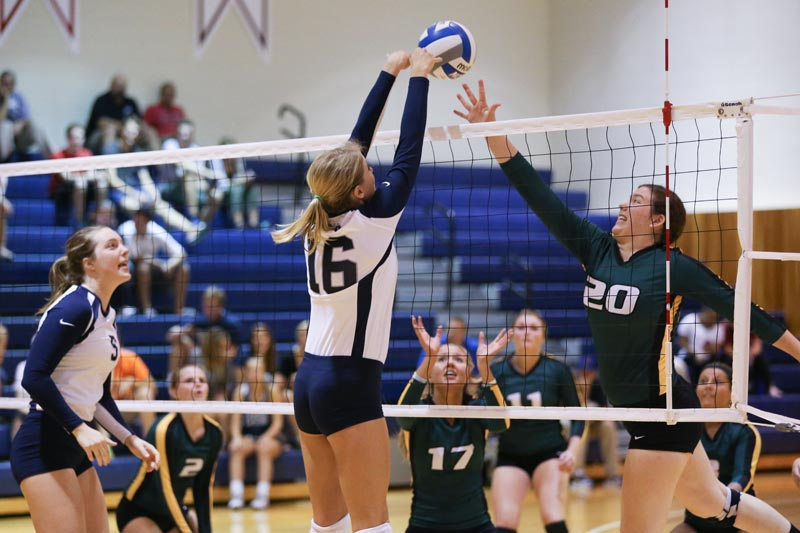 A SUNY Geneseo women's volleyball team member tips the ball over the net during a game.