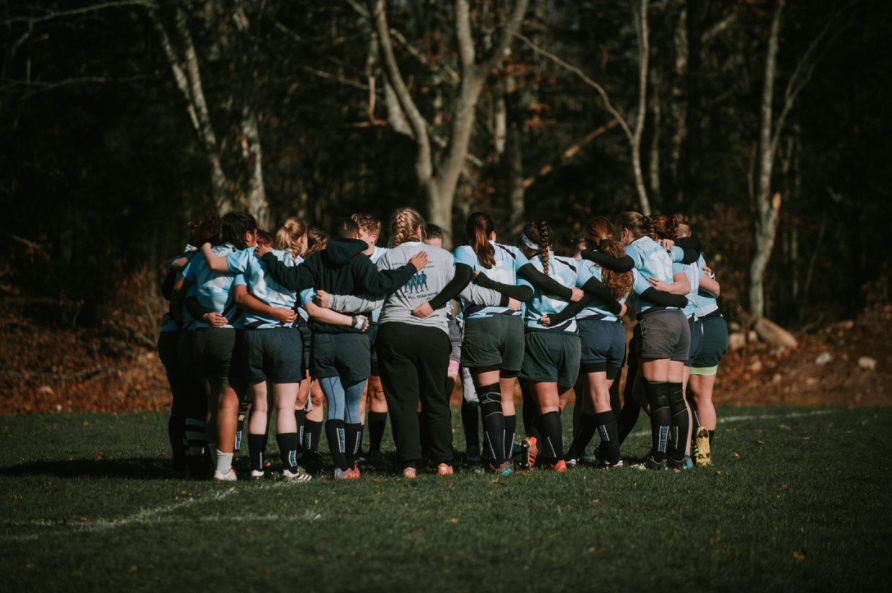 Geneseo Women's Rugby team huddle at the Coast Guard Academy, Fall 2017