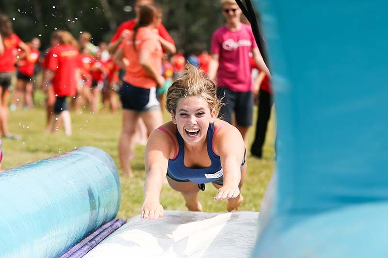 student jumping in waterslide