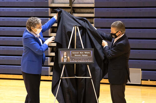 2 government representatives remove black drape from sign