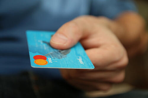 man's hand holding credit card