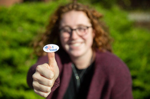 "A student shows an ""I voted"" sticker from a previous year."