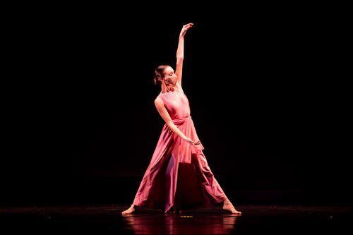 Jillian Johnson '22 dances in a rose-colored costume on stage.