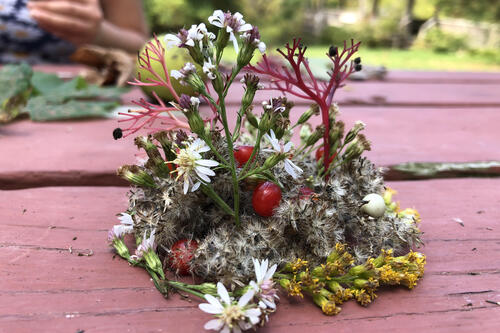 flowers, plants and other foliage is arranged artfully on a picnic table.