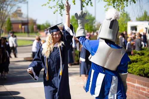 Knight mascot high-fives graduating senior