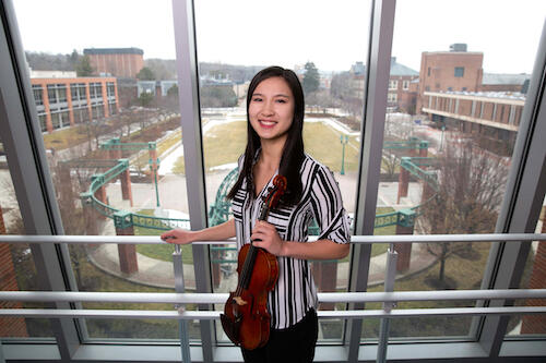 Evelyn Welch holding a violin in the Integrated Science Center.